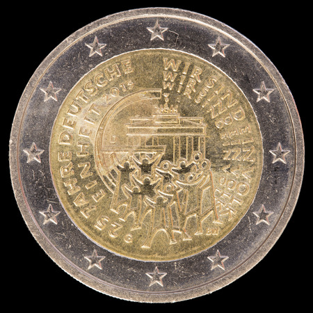 circulated: Commemorative circulated two euro coin issued by Germany in 2015 celebrating the German unification with a crowd around the Brandenburg Gate, symbol of German unity. Image isolated on black background Stock Photo