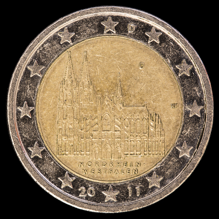 circulated: A commemorative circulated two euro coin issued by Germany in 2011 depicting the Cologne Cathedral located in the federal state of North Rhine-Westphalia. Image isolated on black background. Stock Photo