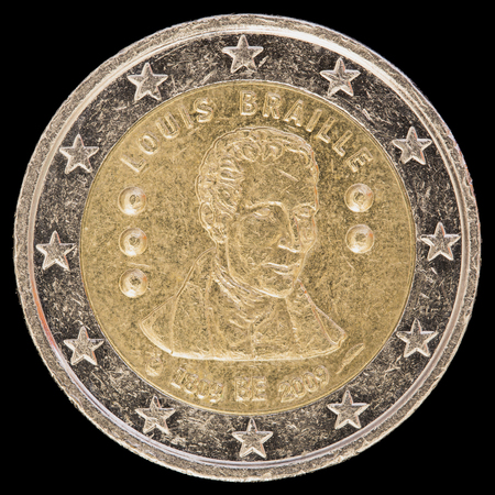 circulated: A commemorative circulated two euro coin issued by Belgium in 2009 and celebrating the 200th anniversary of Louis Braille's birth, inventor of the Braille alphabet. Image isolated on black background. Stock Photo