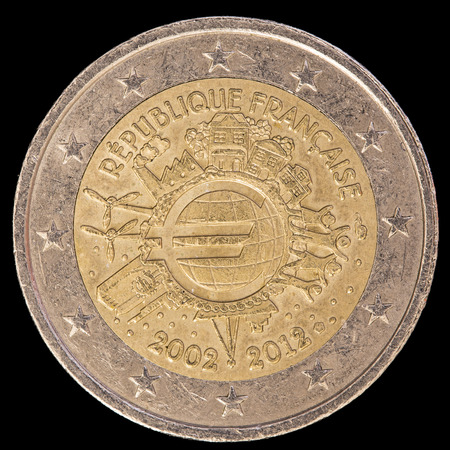 circulated: A commemorative circulated two euro coin issued by France in 2012 and celebrating the ten years of the Euro. Image isolated on black background.