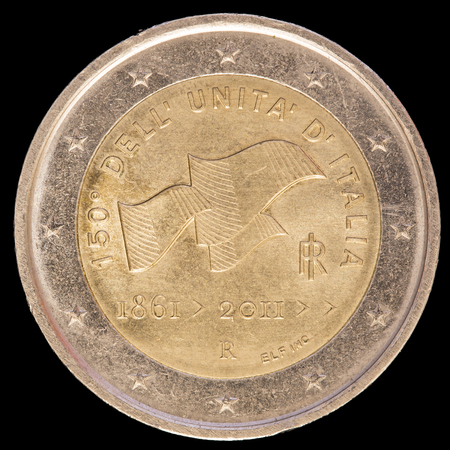 circulated: A commemorative circulated two euro coin issued by Italy in 2011 celebrates the anniversary of unification of Italy with three Italian flags fluttering in the wind. Image isolated on black background.