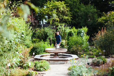 luxuriant: Young Man Walking Around A Fountain in a Luxuriant Garden Stock Photo