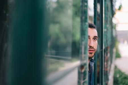 go inside: Beautiful Man Watching Through Dirty Window