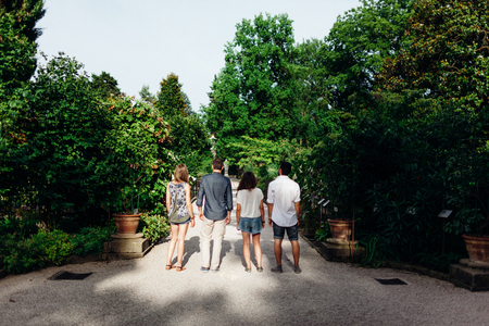 stylish woman: Four Casual Friends Standing In a Row . Botanical Garden One of them is looking back Stock Photo