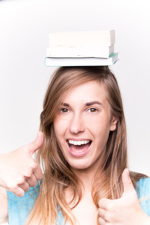 attractive young woman: Attractive young woman balancing a book on her head Whtie Background Stock Photo