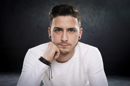sad and numb young brunette man on dark studio background