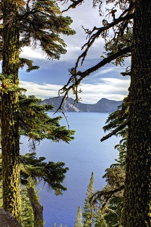 Crater Lake seen through the trees on a hike in Oregon