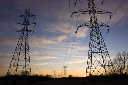 Power lines and towers stretch into the sunset