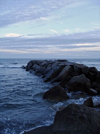 Rocks stretch into the water off of Newport, Rhode Island