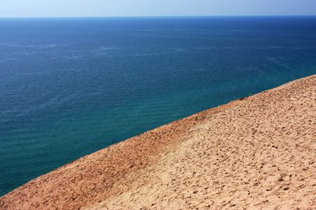 Sand dune meets the water on the edge of Lake Michigan