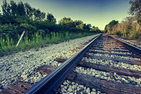 Angled train tracks fade off into the horizon of the landscape