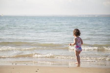 ni�as peque�as: ni�o considerando enering el mar fr�o