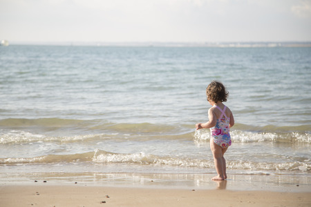 little girl swimsuit: toddler considering enering the cold sea