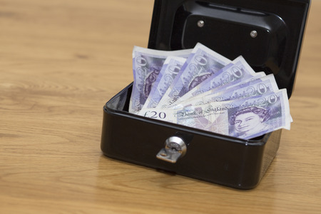 tabel: Money in security box on wooden tabel