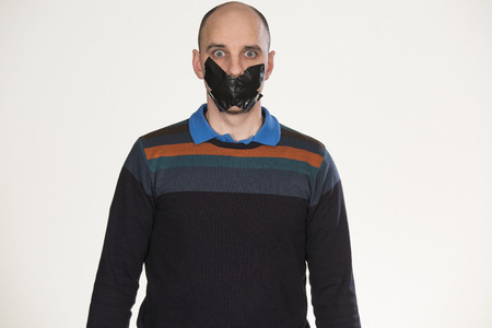 gagged: man gagged by tape over mouth Stock Photo