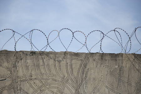 prison wall: Barbed wire on top of prison wall