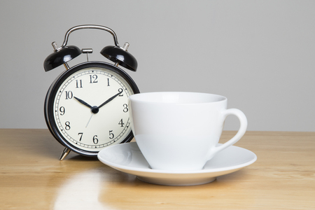 beat the clock: Alarm and cup of tea on wooden table