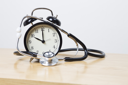 facing to camera: Alarm clock facing camera With Stethoscope wrapped around it.
