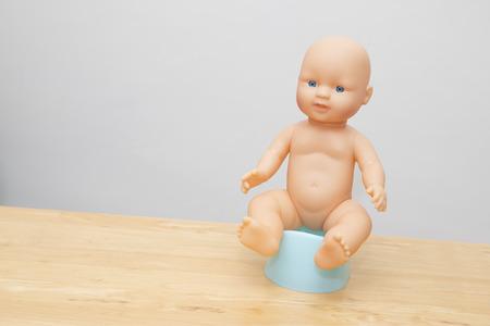 Doll sitting on potty to illistrate potty training