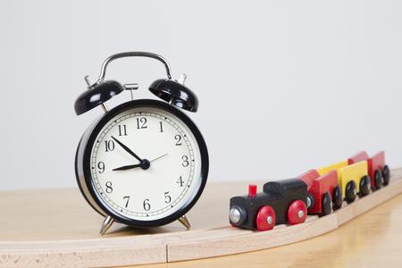 delays: Train on wooden track passes alarm clock - delays concept