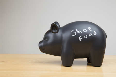 Piggy bank with chalk writting that spells shoe fund Stock Photo