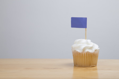 butter icing: Blank flag sitting on top of a cupcake on a wooden table