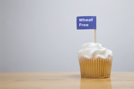 fairy cake: Iced fairy cake with Wheat free written on an allergy advice flag Stock Photo
