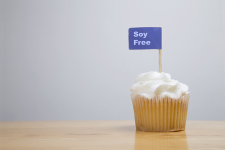 butter icing: Iced fairy cake on wooden table with Soy Free allergy advice flag