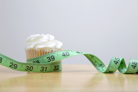 butter icing: healthy eating concept, cupcake wrapped in a measuring tape