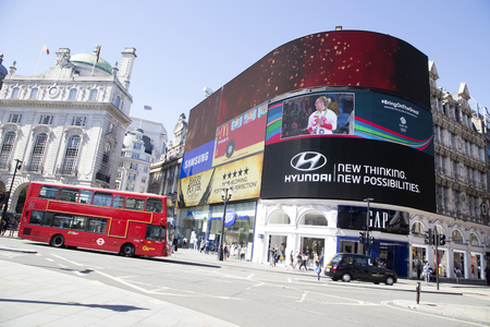 piccadilly: LONDON, UK - AUG 12, 2016. Red bus passing big screens in Piccadilly circus Editorial