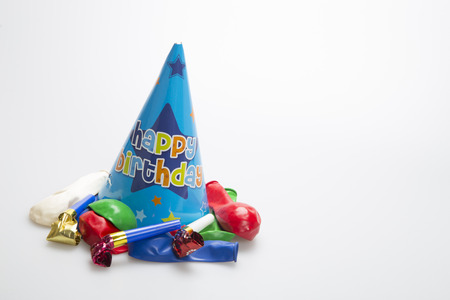 favour: Blue party hat on a white background with ballons and party blowers