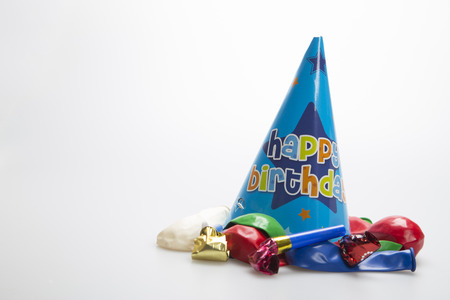 Party hat on white background with balloons and party blowers