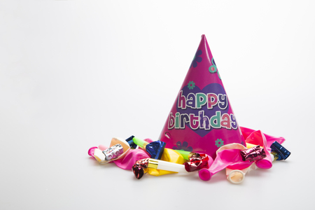 favour: Birthday party hat on white background with balloons and party blower Stock Photo