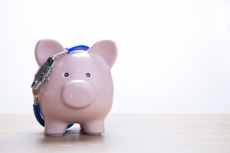 locked: Piggy bank facing camera with locked chain Stock Photo