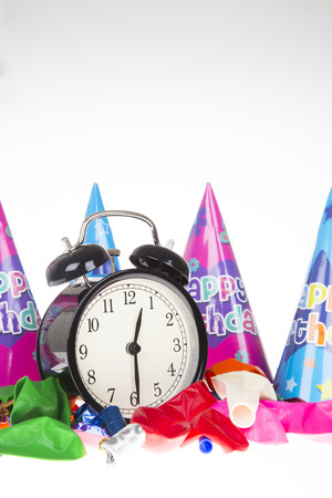 Kids party concept with alarm clock surrounded by party hats, ballons and blowers