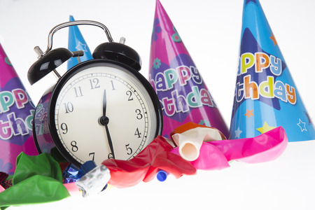 Low angle view of alarm clock surrounded by ballons and party hats