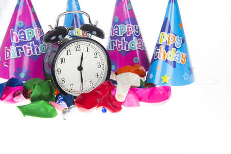 Alarm clock surrounded by party hats, balloons, and party blowers