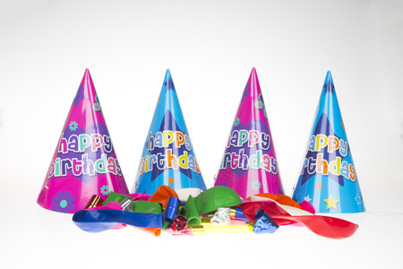 Party hats lined up behind ballons and party blowers