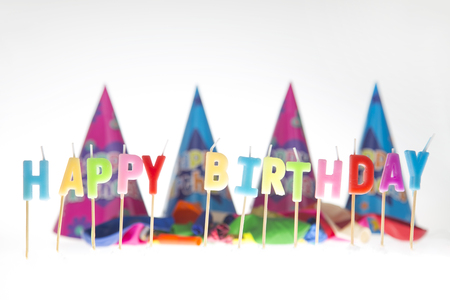 Happy birthday writen in candleswith party hats in background Stock Photo