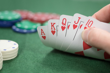 Poker player with a winning hand lifting the corner of the cards off the table to display a royal straight flush in hearts