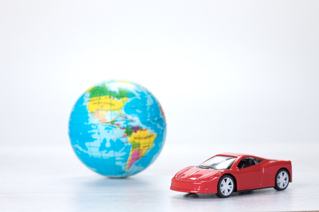 Red toy model car with a world globe in a concept of travel and destinations or of saving the planet through using eco-friendly fuels, with copy space