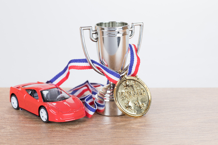 Red model supercar with a trophy and medal in a concept of wining a championship motor race or competition with copy space alongside Stock Photo