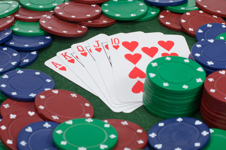 Playing cards on table beside stacked poker chips displayed as a straight as seen from a close up view Stock Photo