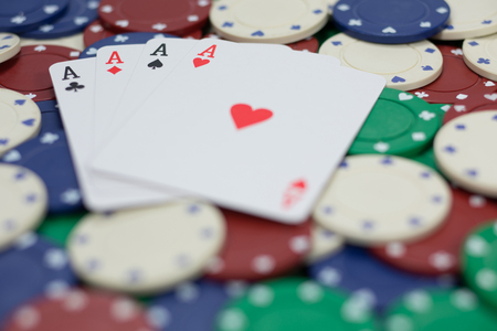 Gambling and casino background showing a poker hand of four of a kind aces with the cards fanned on betting chips viewed low angle wit shallow dof Stock Photo