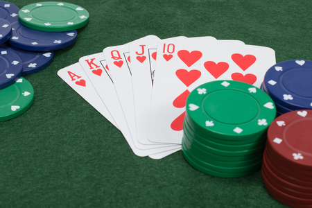Close up view of five playing cards showing flush placed on green felt covered table as seen from an overhead view