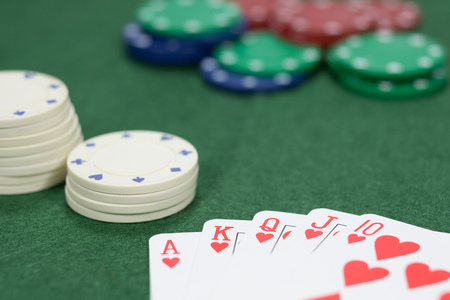 Concept of gambling in a casino on a winning streak playing poker with a hand showing a royal straight flush on green baize with focus to a stack of chips alongside Stock Photo