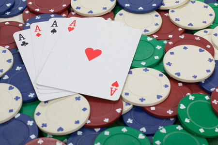 Close up view of four playing cards with aces on them arranged on a background of poker chips