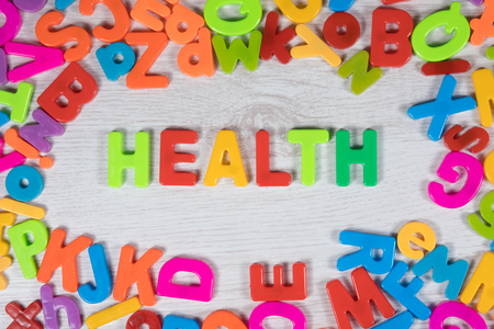 Plastic magnet letters in bright colors make border around the word health against a painted wood background Stock Photo