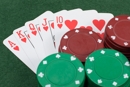 Four stacks of poker chips colored red and green beside five playing cards placed on a table