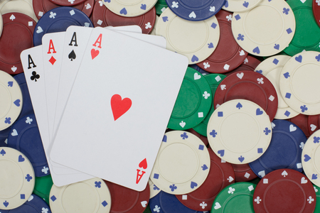 Large wager of poker chips create background for playing cards with aces on them